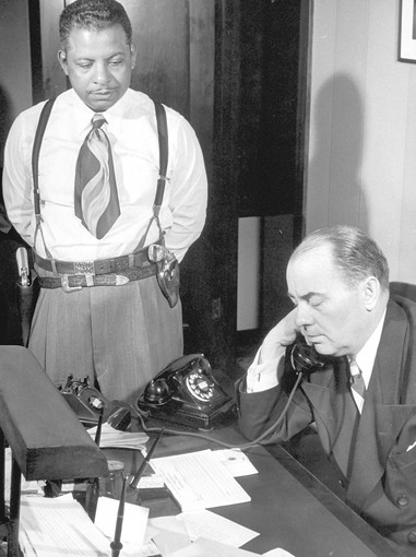 Chicago police Officer Sylvester Washington, known as Two-Gun Pete, confers with Chicago ward boss Joseph T. Plunkett. (Joseph Scherschel, Time & Life Pictures/Getty Image)