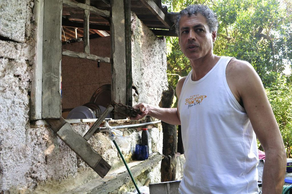 José Claudio Pinto holds the lock that was once used to keep the windows of quilombo Sacopã's kitchen shut. (Carolina Ramirez/The Huffington Post)