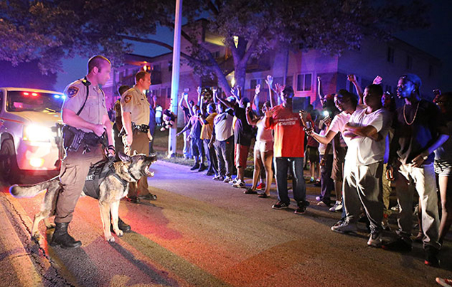 St. Louis County police officers confront a crowd in Ferguson after Brown's shooting. / David Carson/St. Louis Post-Dispatch/MCT/ZUMA Press