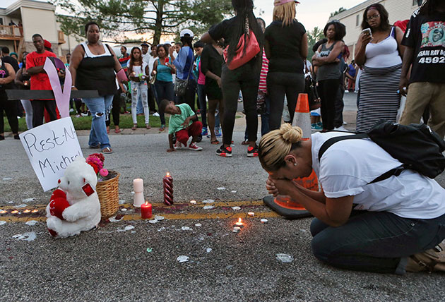 A woman prays at the site on Sunday, August 10, where Michael Brown was killed the previous afternoon. J.B. Forbes/St. Louis Post-Dispatch/AP