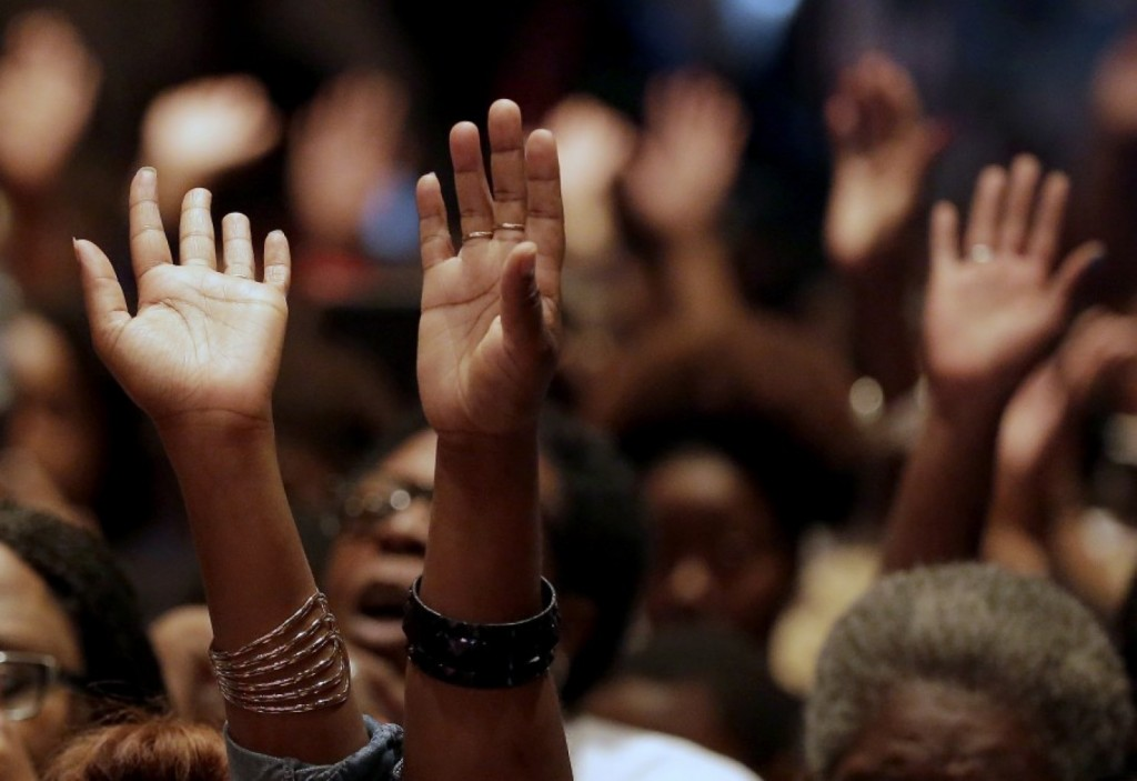 People raise their hands during am August rally for Michael Brown in Ferguson, Mo. (AP Photo/Charlie Riedel)
