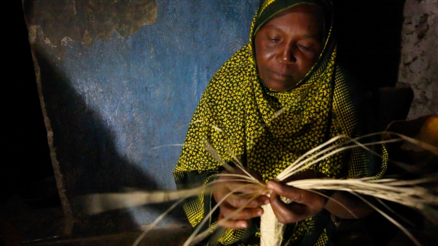 Kanoa Sharif Haji, a 45 year old mother of eight, weaves reed mats at night under a bright solar powered LED light at her home in Matemwe. This new work at night earns her family an extra fifteen dollars a month, a huge amount in these parts. Credit: Sam Eaton