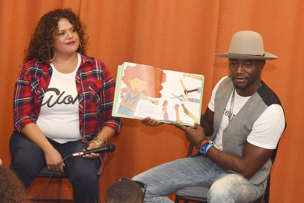 Fashion designer Sonia Smith-Kang sits with actor Taye Diggs as he reads his book, Mixed Me, to children in Los Angeles in 2015. Vivien Killilea/Getty Images for Mixed Up Clothing Inc.