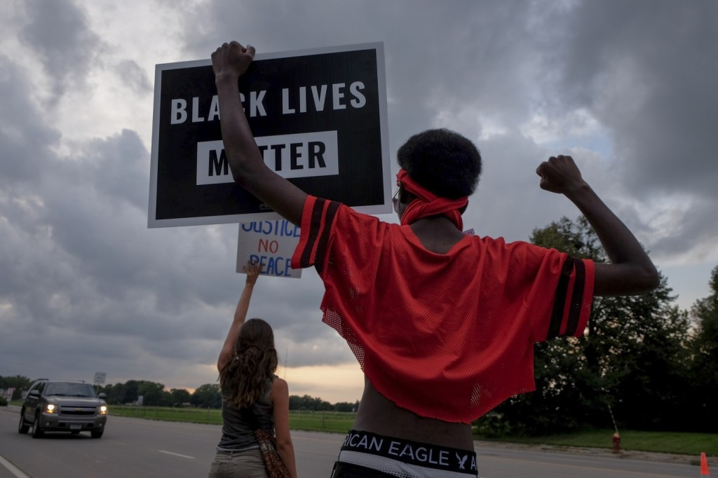 Protesters hold signs at an Aug. 29 vigil for Philando Castile near the site where he was pulled over ostensibly for a broken taillight on July 6 in Falcon Heights, Minn. (Jahi Chikwendiu/The Washington Post)