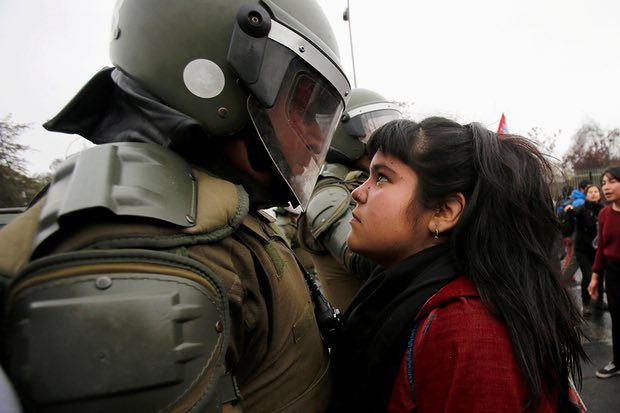 A demonstrator faces down a riot policeman during a protest marking the country's 1973 military coup in Santiago, Chile on 11 September 2016. Photograph: Carlos Vera/Reuters
