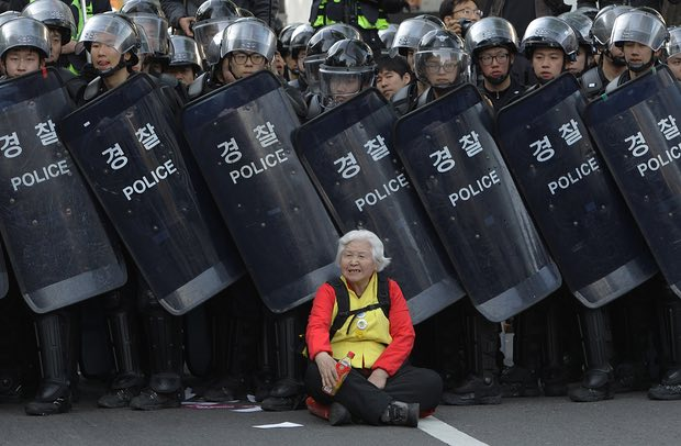 A woman sits in front of riot police blocking the road to protect protesters during an anti-government march on 24 April 2015 in Seoul, South Korea. Photograph: Chung Sung-Jun/Getty Images