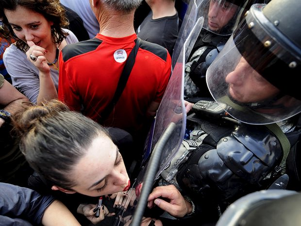 Jasmina Golubovska does her lipstick in the shield of a policeman in front of a government building in Skopje, Macedonia, on 5 May 2015. Photograph: Ognen Teofilovski/Reuters