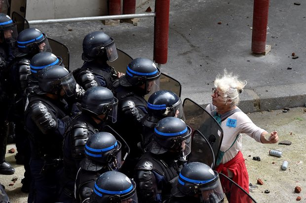 A woman stands in front of police officers as they block access to a street during a protest against proposed labour reforms in Paris on 14 June 2016. Photograph: Alain Jocard/AFP/Getty Images