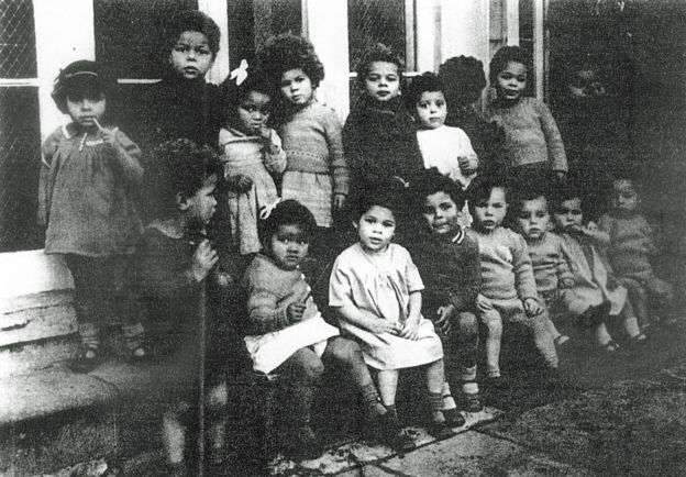 Image caption - Deborah Prior, front row, in the light dress, lived in Holnicote House in Somerset along with other mixed-race children - the photograph was used to attract potential adoptive parents